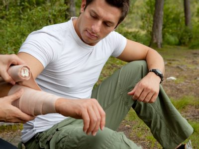 A woman applying an arm bandage on a male camper - focus on male face
