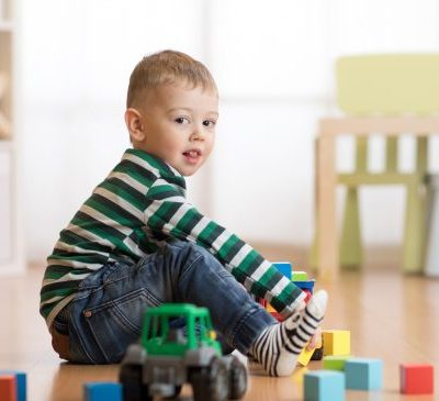 Lovely child boy playing with building cubes in kindergarten, siting on floor